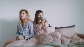 Two young women or a lgbt couple are drinking coffee in the bed. A blonde young woman is bringing her beautiful brunette partner coffee or tea in bed in bright stock video footage