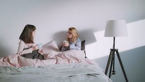 Two young women or a lgbt couple are drinking coffee in the bed. Two pretty best friends females, a blonde and a brunette are drinking coffee and have woman talk stock video footage