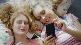 Two young women lie on the bed`s head-to-head. Enjoy smartphone, listen to music. Top view, beautiful hair lying on a. Pillow. HD video top view stock footage