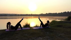 Two Young Women Lie on Mats, Raise One Leg Each, Smile, at Sunset. Two Young Women Lie on Mats Near in Front of Each Other, Raise One Leg up and Make Round stock footage