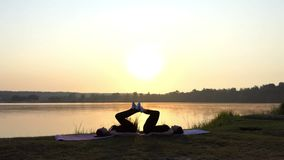 Two Women Lie on Mats And Make a House With Sun Figure in Artistic Way. Two Young Women Lie on Yoga Mats and Make a House With Sun Figure, While Touching the stock footage