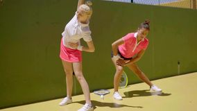 Two young women limbering up before tennis. Two young women limbering up doing stretching exercises before playing a tennis match stock video footage