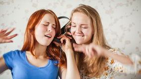 Two Young Women Listens to Music. The young women likes to listen to music through headphones stock video
