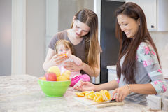 Two young women and little girl in the kitchen. Royalty Free Stock Photography