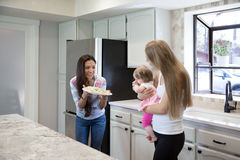 Two young women and little girl in the kitchen. Stock Photos