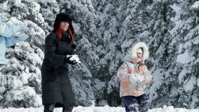 Two young women, little girl throwing snowballs. A family with child while enjoying in the idyllic winter time soroundings stock footage