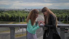 Two young women look at each other`s manicure on the nails. On the street. Two young women look at each other`s manicure on the nails. Meeting two friends, slow stock footage