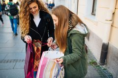 Two young women look at shopping bags stock photography
