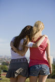 Two young women looking across the city, rear view Stock Photography