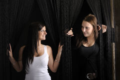 Two young women looking from behind a cord curtain Royalty Free Stock Image