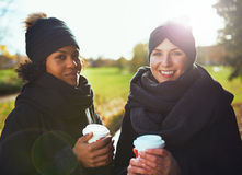 Two young women looking at camera, smiling while holding coffee to go Stock Photo