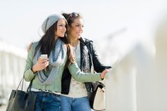 Two young women looking over a dock fence Royalty Free Stock Photography