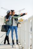 Two young women looking over a dock fence and pointing in a dire Royalty Free Stock Image