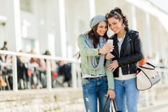 Two young women looking at the phone while being close to eatch Stock Photo