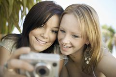 Two young women looking at pictures on digital camera in backyard front view Royalty Free Stock Image