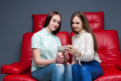 Two young women looking at pictures on phone Stock Images