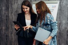 Two young women looking at screen of tablet PC. stock photography