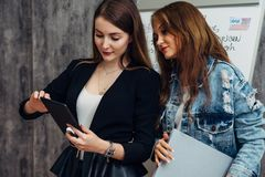 Two young women looking at screen of tablet PC using mobile application. Two young women looking at screen of tablet PC using mobile application stock photo
