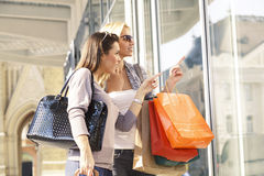 Two young women looking in showcase Stock Image