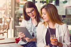 Two young women looking at a tablet Stock Photos