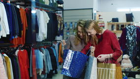 Two young women looking at their purchases in bags. Then, out of the store. successful Shopping stock video