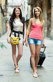 Two young women with luggage Stock Images