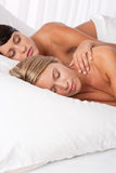 Two young women lying down in white bed Stock Photography