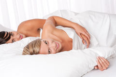 Two young women lying down in white bed Stock Photos