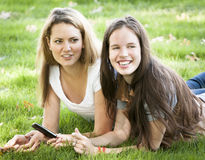 Two young women lying on the ground Stock Photos