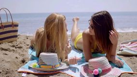 Two young women lying sun tanning on a beach. Two attractive young women in bikinis lying on a towel together sun tanning on a beach chatting and smiling with stock footage