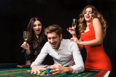 Two young women and man behind roulette table on black background Royalty Free Stock Photo