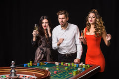Two young women and man behind roulette table on black background Stock Image