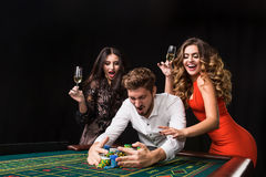 Two young women and man behind roulette table on black background Royalty Free Stock Image