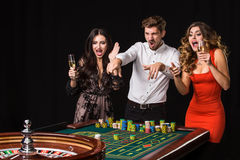 Two young women and man behind roulette table on black background. Two young women and men behind roulette table on black background. Emotions players royalty free stock photos