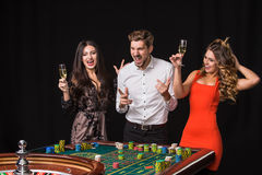 Two young women and man behind roulette table on black background. Two young women and men behind roulette table on black background. Emotions players stock photography