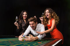 Two young women and man behind roulette table on black background Royalty Free Stock Photography