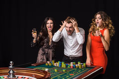 Two young women and man behind roulette table on black background Stock Photo
