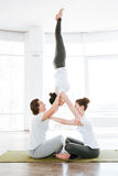 Two young women and man doing acrobatic yoga position Royalty Free Stock Image