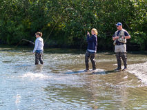 Two young women and a man guide salmon fishing in small river in Stock Photos