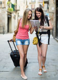 Two young women with map Stock Images