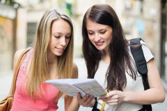Two young women with map Royalty Free Stock Images
