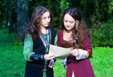 Two young women in medieval dresses reading papers Stock Images