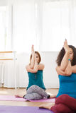 Two young women meditating with crossed arms and legs Royalty Free Stock Photography