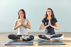Two young women meditating in lotus pose with hands in namaste Stock Photo