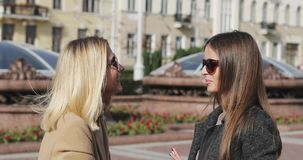 Two young women meeting in a downtown and talking with emotions. Blonde and brunette girlfriends have a conversation outdoors stock video