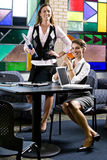Two young women meeting with laptops at table Stock Photo