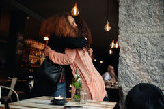 Two young women meeting at a restaurant Royalty Free Stock Photo