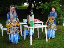 Two young women in national costumes pose for photos. Stock Photography