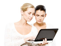 Two young women with netbook royalty free stock photography