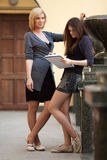 Two young fashion women with notebook Royalty Free Stock Photos